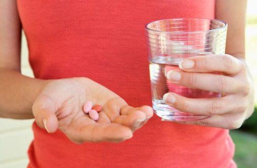 Женщина принимает витамины